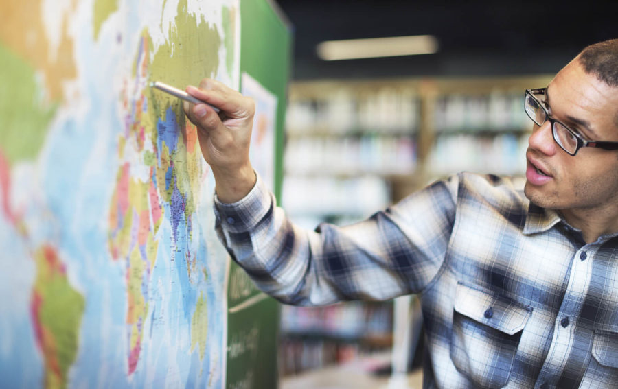 teaching assistant writing on map